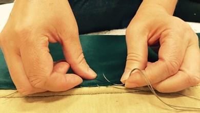 Händer som arbetar med en textilväv.