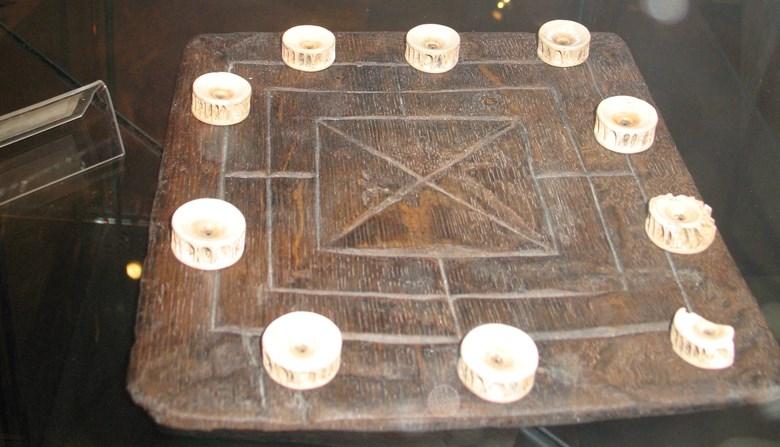 Kvarnspel med spelbrickor av hajkotor på Lödöse museum.