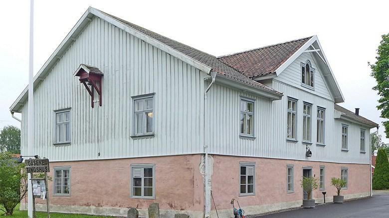 Gäsene tingshus i Herrljunga. En vit träbyggnad med fundament i rosa sten.
