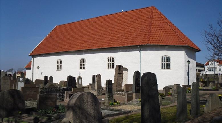 Öckerö gamla kyrka med kyrkogården i förgrunden.