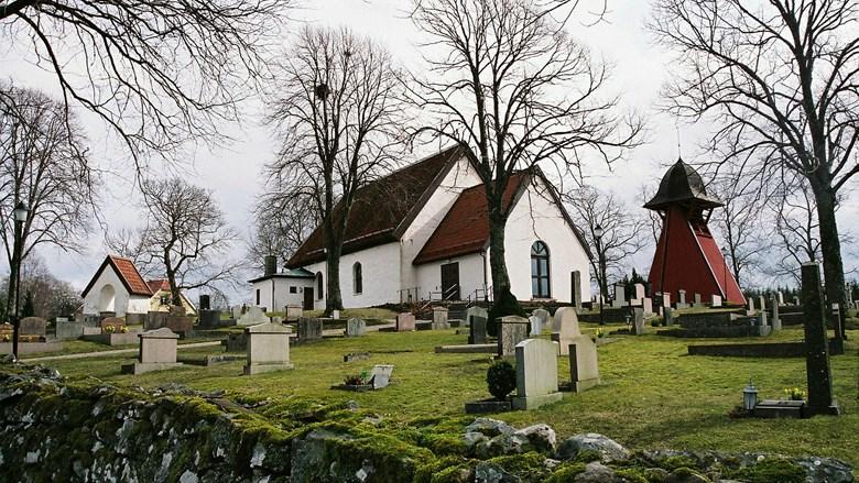 Vy över Stora Lundby kyrka och kyrkogård med stiglucka och klockstapel
