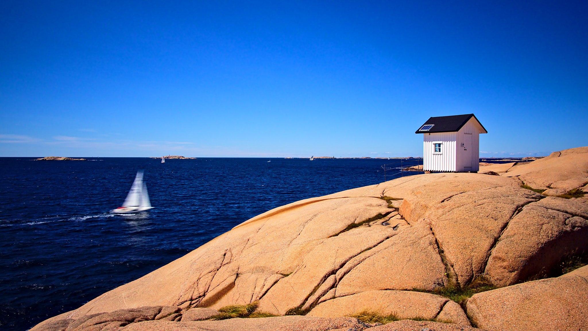 Litet, vitt fyrhus på granitklippor vid havet.