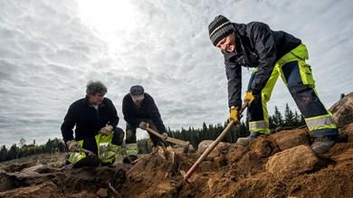 Tre arkeologer gräver i marken, i bakgrunden en molnig himmel där solstrålar silar igenom