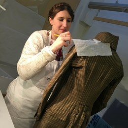 Conservator student Valentine working with a men's tailcoat from the 1790s'.