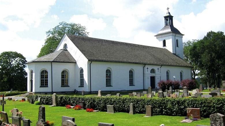 Kyrkogård med vit putsad kyrka