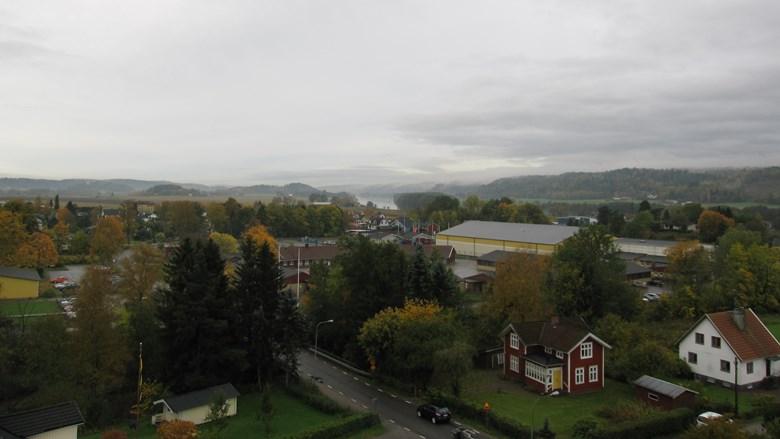 Utsikt över litet samhälle med bergskullar och vattendrag i bakgrunden
